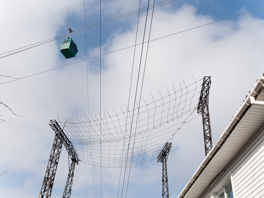 Cable car passes over a house in Almaty, Kazakhstan