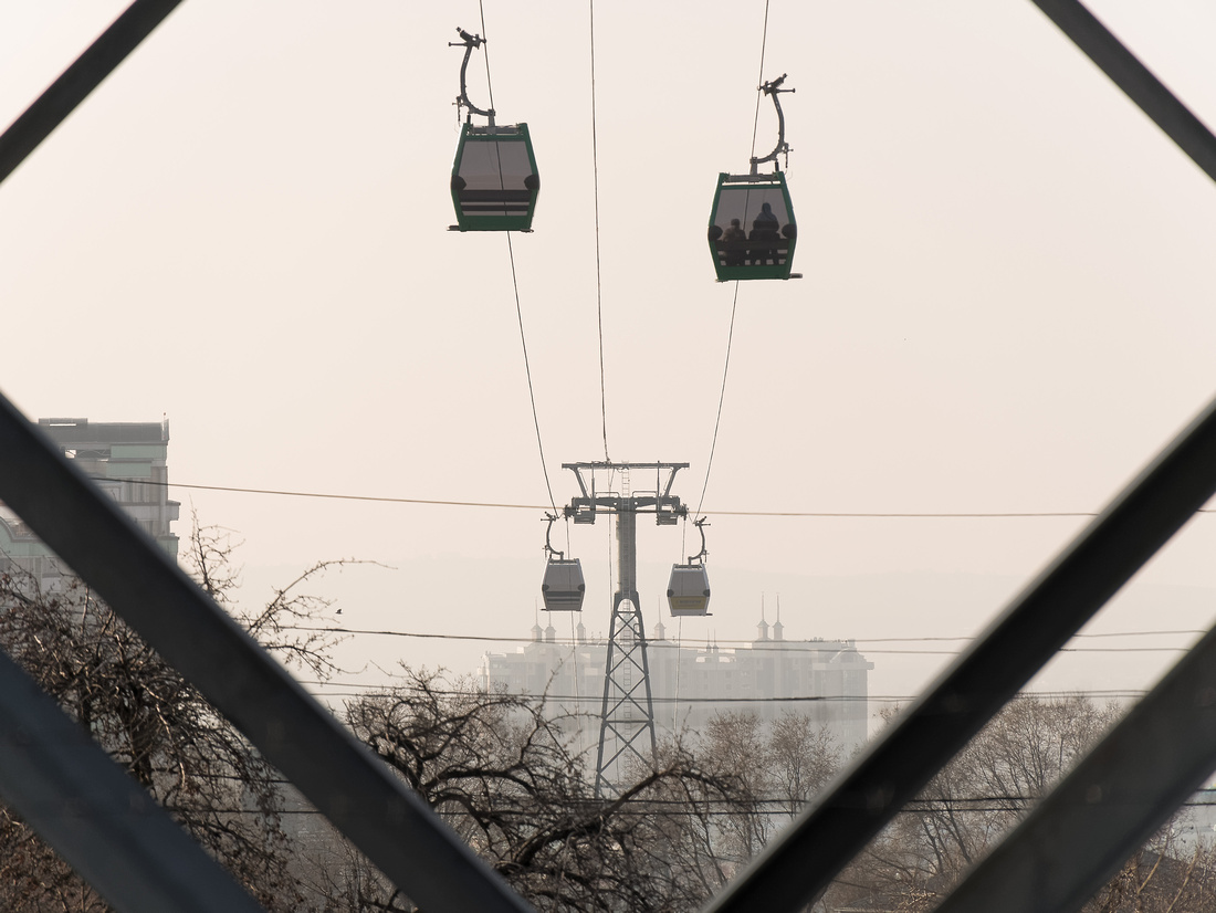 Seen from below, cable car descends with apartment buildings in the background.