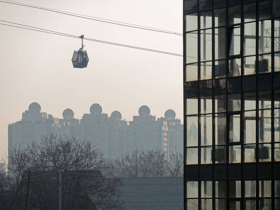 Cable car with Dostyk Towers apartment buildings in the background.