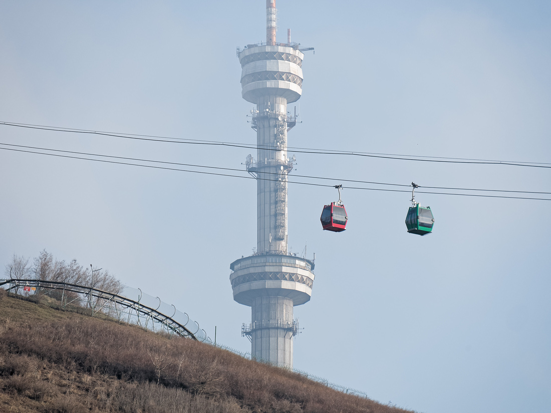 Cable car ascends Kok Tobe in Almaty, Kazakhstan, with TV tower in the background.
