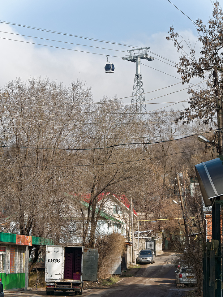 A cable car passes over a residential neighborhood in Almaty, Kazakhstan.