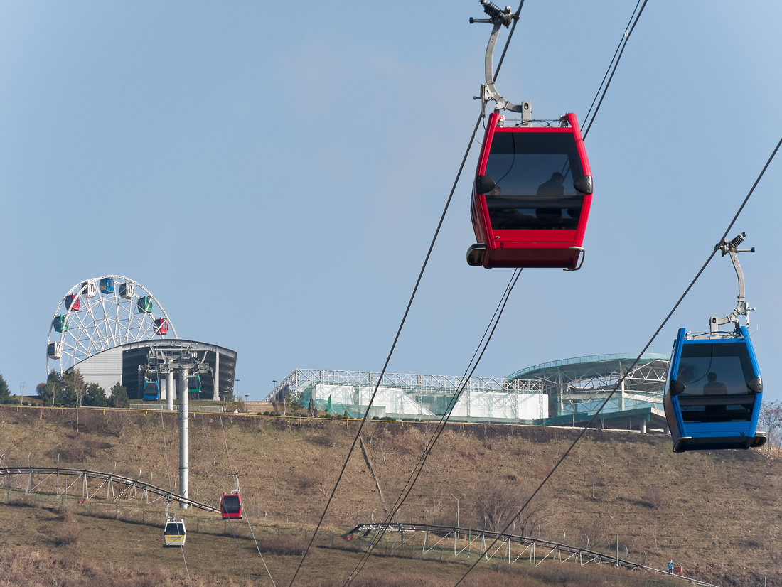 Cable car ascends Kok Tobe in Almaty, Kazakhstan, with Ferris wheel and amusement park in background.